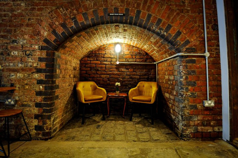 Two chairs set into a little brick alcove. Cosy, warm and romantically lit.