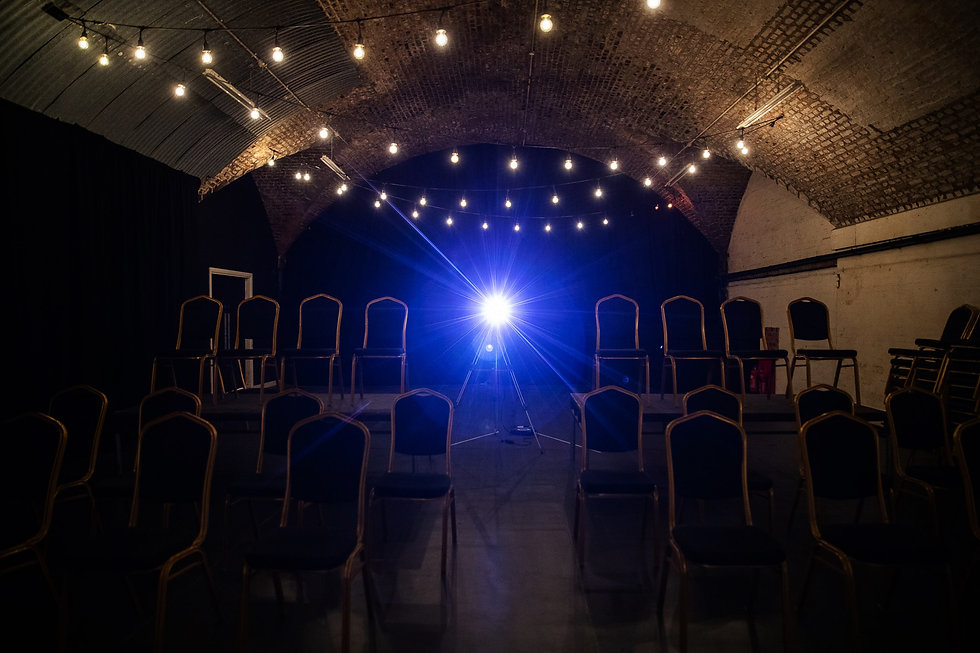 Our studio space. Rows of chairs at different heights, festoon lighting lit dimly and a projector.