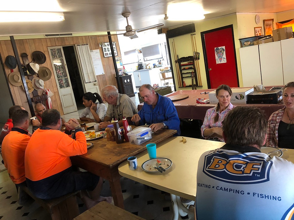 Members of The Oasis Townsville and the farmers being assisted sitting down for a meal and a good talk.