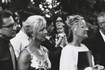 Family watching bride and groom exchange vows under trees at the Ottawa Arboretum by Melanie Mathieu Photography. Melanie is an ottawa photographer with a candid, lifestyle approach.