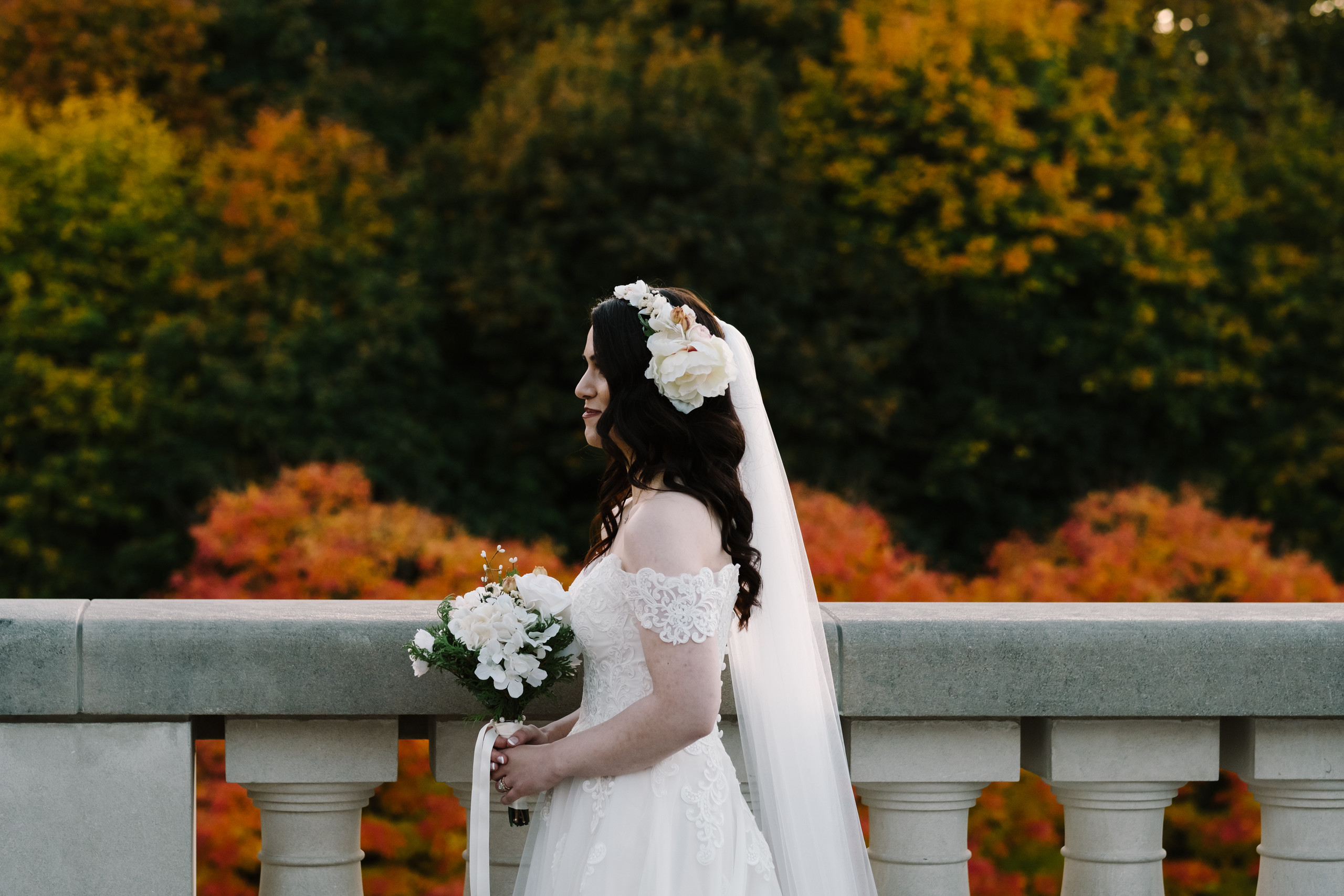 Fall wedding in Ottawa at the Château Laurier. Photo of bride with her veil and bouquet posing with the Fall foliage in the background. Photo by Melanie Mathieu Photography.