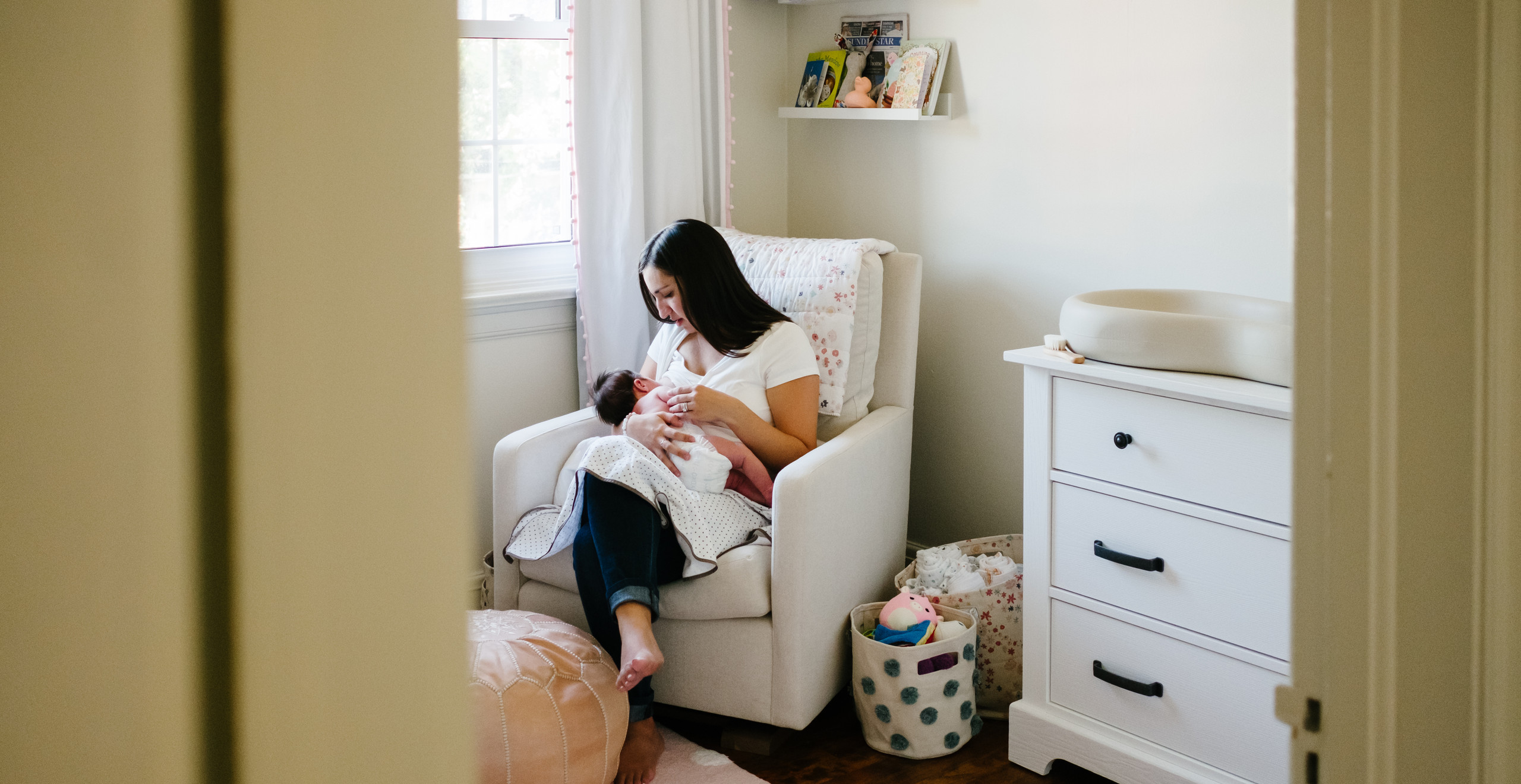 Mother nursing baby girl during newborn photography session in Ottawa Gatineau.