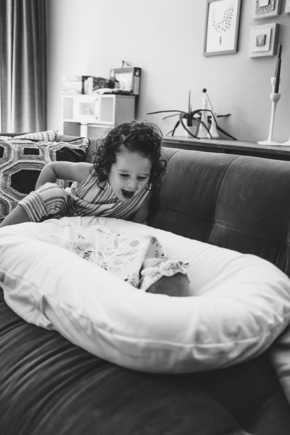 baby girl with big sister looking on by Melanie Mathieu Photography, Ottawa Gatineau lifestyle and newborn photographer