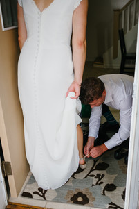 Groom fixing bride's shoes on wedding day. Photo by Melanie Mathieu Photography. Melanie is an Ottawa Photographer who focuses on candid and lifestyle wedding photoraphy.