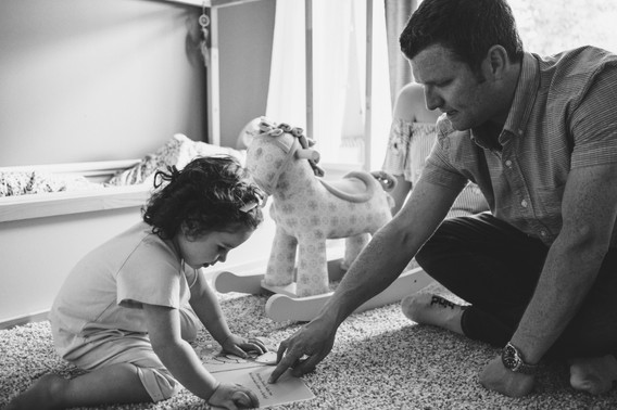 dad and daughter reading together during ottawa in home family photo session with ottawa gatineau lifestyle family photographer Melanie Mathieu