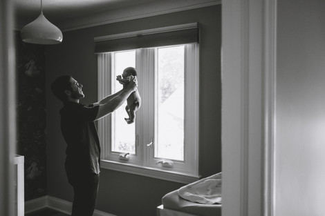 Father holding baby boy in nursery during in-home candid newborn photography session with Melanie Mathieu Photography. Melanie is an Ottawa family photographer.