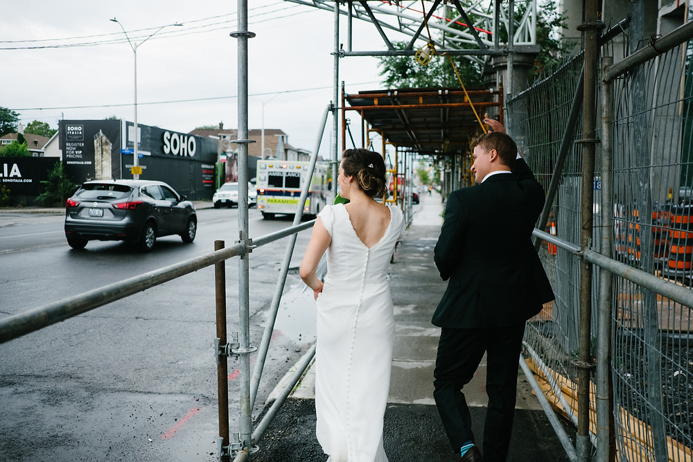 Bride and groom waiving as they walk down a street in Little Italy in Ottawa after their ceremony at the Arboretum. Rainy day wedding ceremony in Ottawa. Photo by Melanie Mathieu, Ottawa photographer.