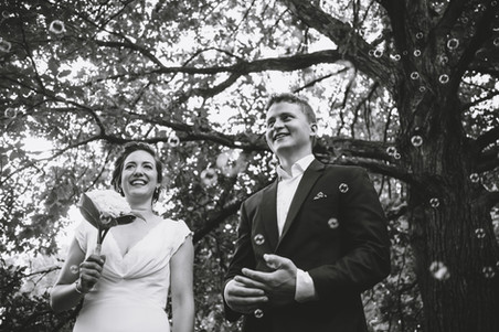 Couple just married at the Ottawa Arboretum while family blows bubbles. Photo by Melanie Mathieu, Ottawa family and wedding photographer.