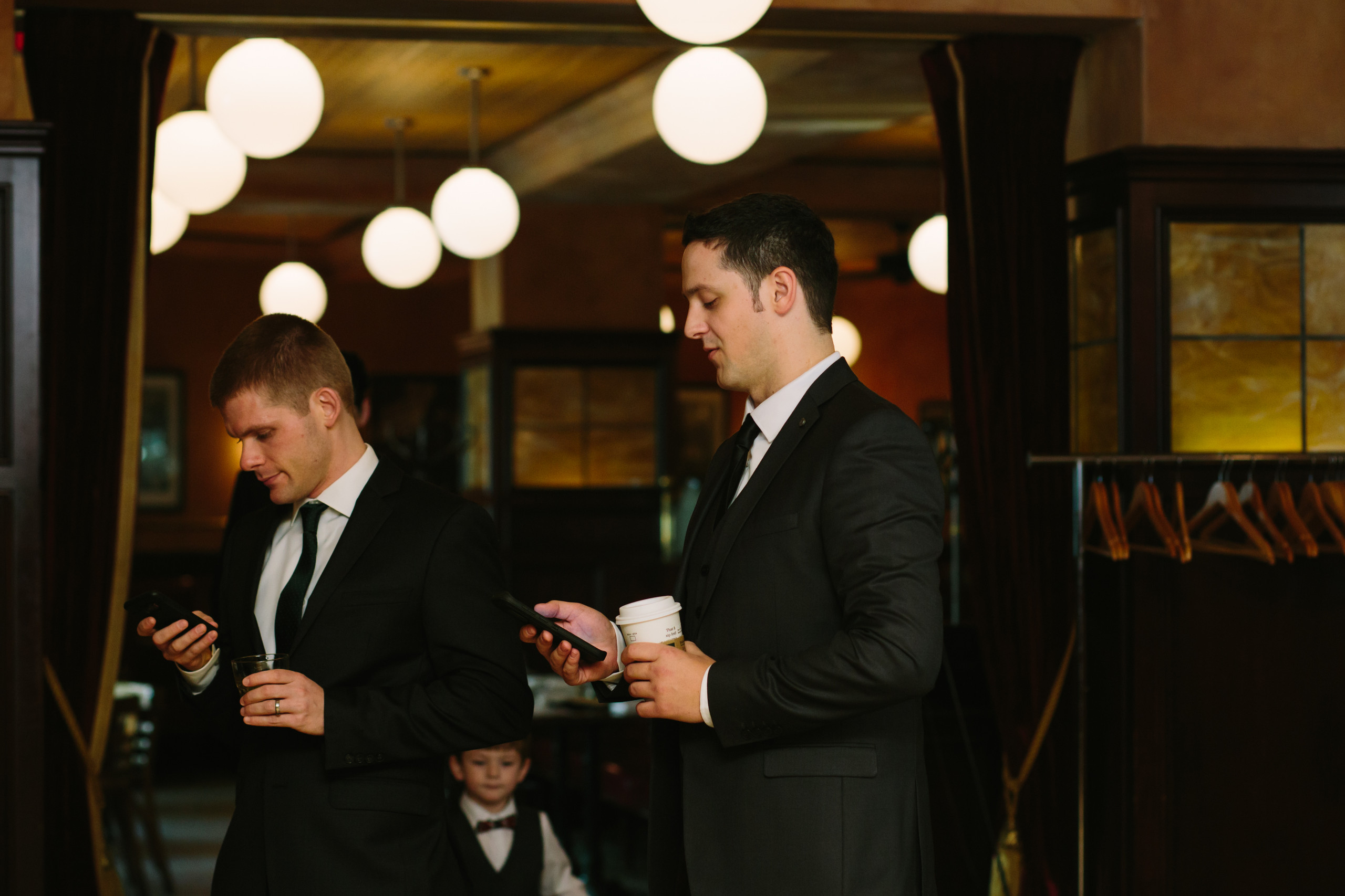 Groom and groomsmen on their phones waiting for wedding ceremony to start at the Metropolitain Brasserie.