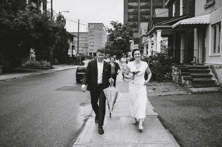Ottawa bride and groom walking down a street in Little Italy towards their wedding ceremony at the Arboretum. Photo by Melanie Mathieu, Ottawa wedding photographer / photographe mariage Gatineau Ottawa