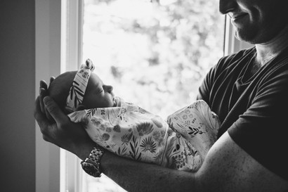 baby girl in dad's arms by Melanie Mathieu, Ottawa Gatineau family and lifestyle photographer.