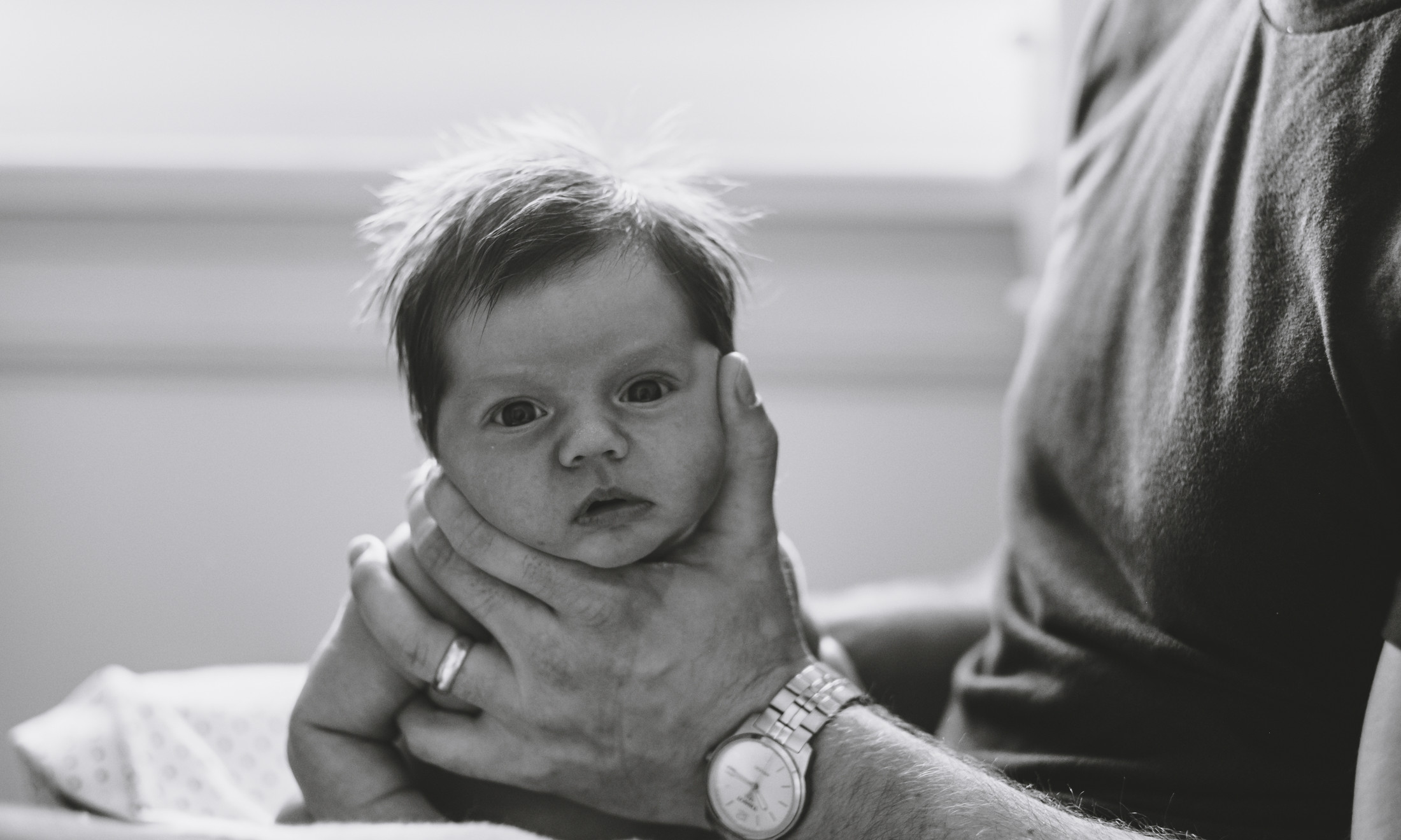 Newborn baby girl being burped by her dad during candid family photography session in Ottawa Gatineau.