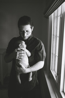 Father holding newborn baby boy during newborn photography session in Ottawa Gatineau. Photo by Melanie Mathieu Photography + Films, Melanie is an Ottawa newborn photographer.