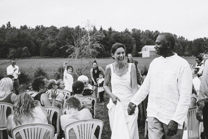 Guests throwing rice at the bride and groom following an outdoor farm wedding ceremony in Gatineau QC. Captured by Melanie Mathieu, ottawa gatineau wedding photographer.