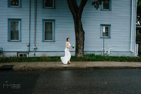 Ottawa bride walking down a street in Little Italy before the outdoor wedding ceremony at the Arboretum. Candid photo by Melanie Mathieu, Ottawa photographer.
