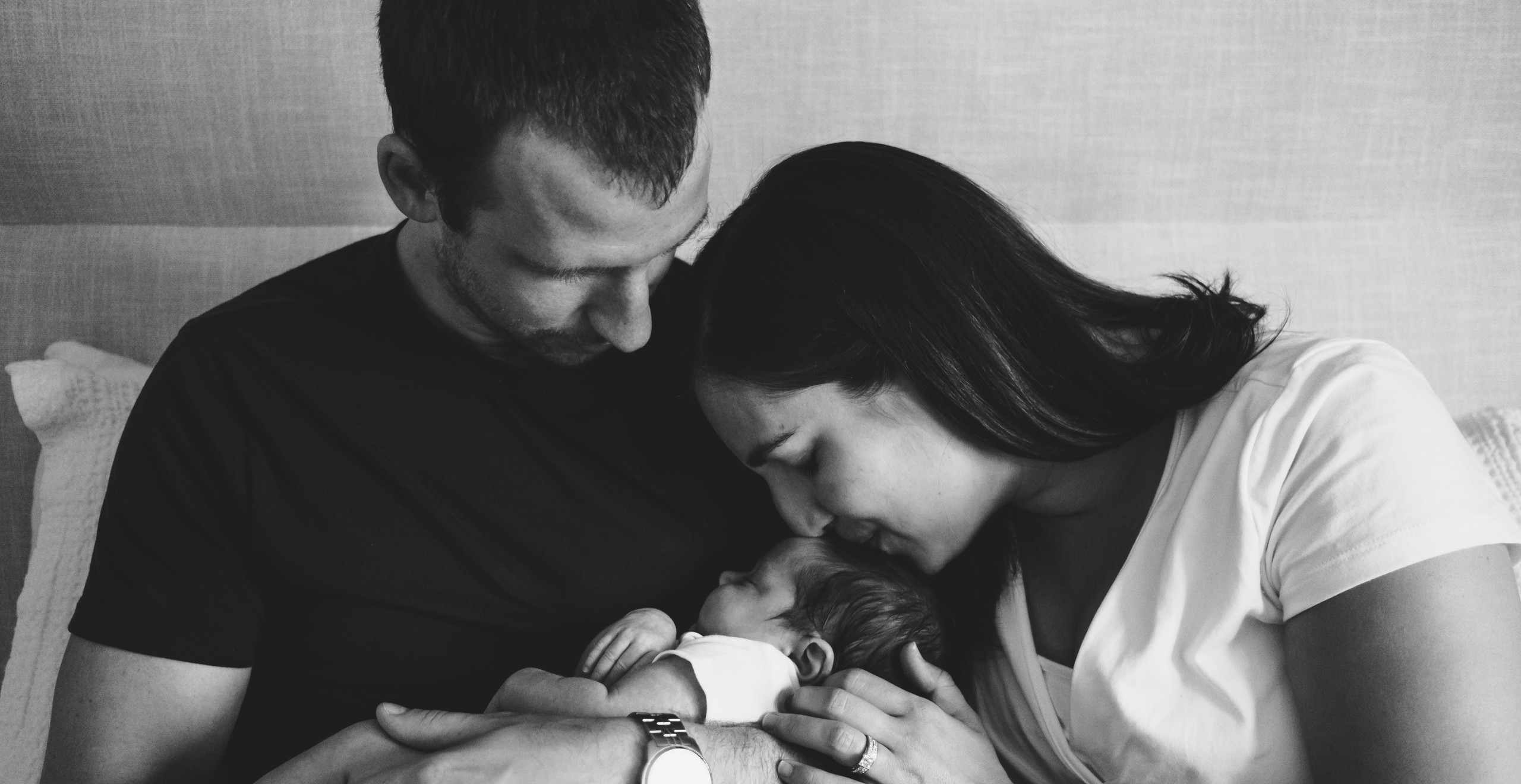 Parents holding and kissing baby girl during newborn photography session in Ottawa Gatineau. Photo by Melanie Mathieu Photography + Films, Ottawa Gatineau family photographer.
