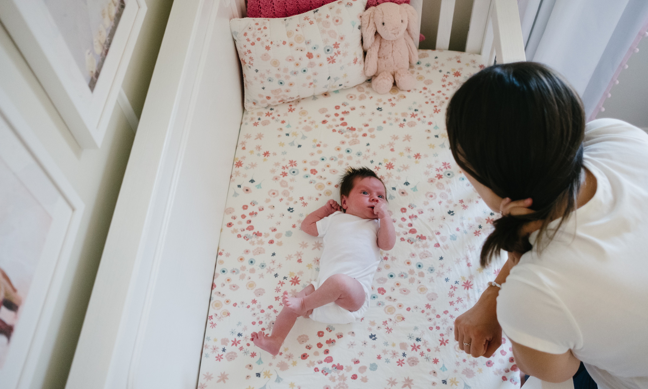 Mother looking at newborn baby girl in crib. Photo from Ottawa newborn photography session.