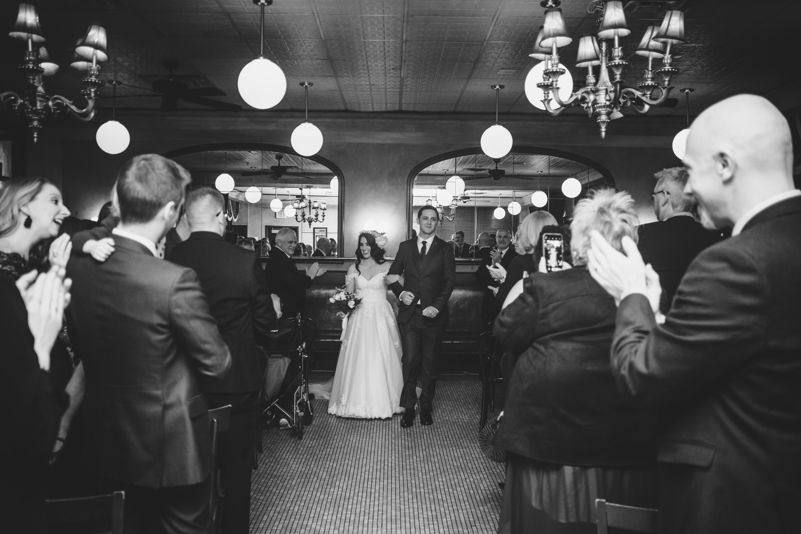 Bride and Groom walking down the aisle as a married couple following their wedding at the Metropolitain Brasserie. Photo by Melanie Mathieu Photography.