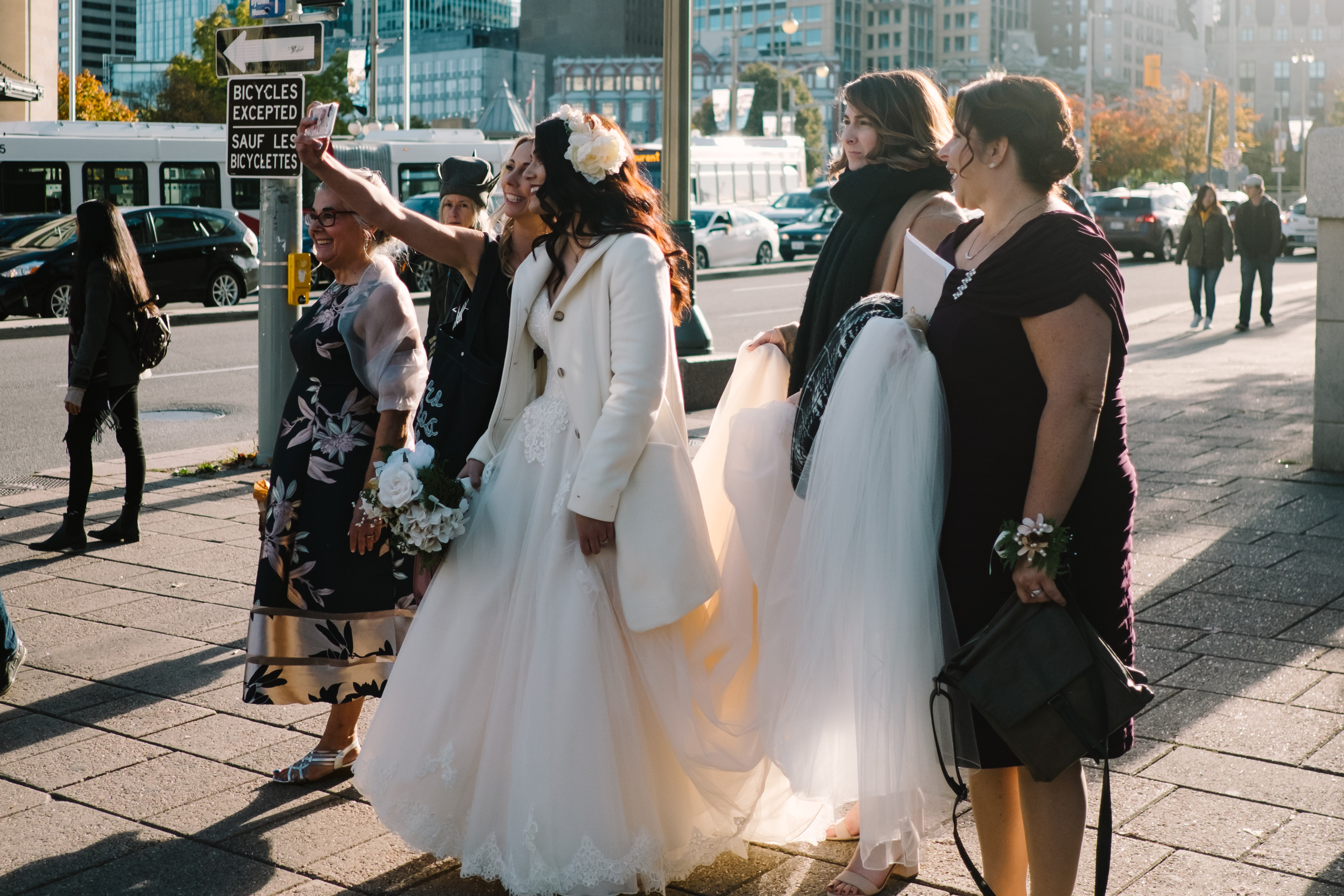 Candid photo of bride and her bridal party taking a selfie downtown Ottawa before wedding ceremony at the Metropolitain Brasserie.