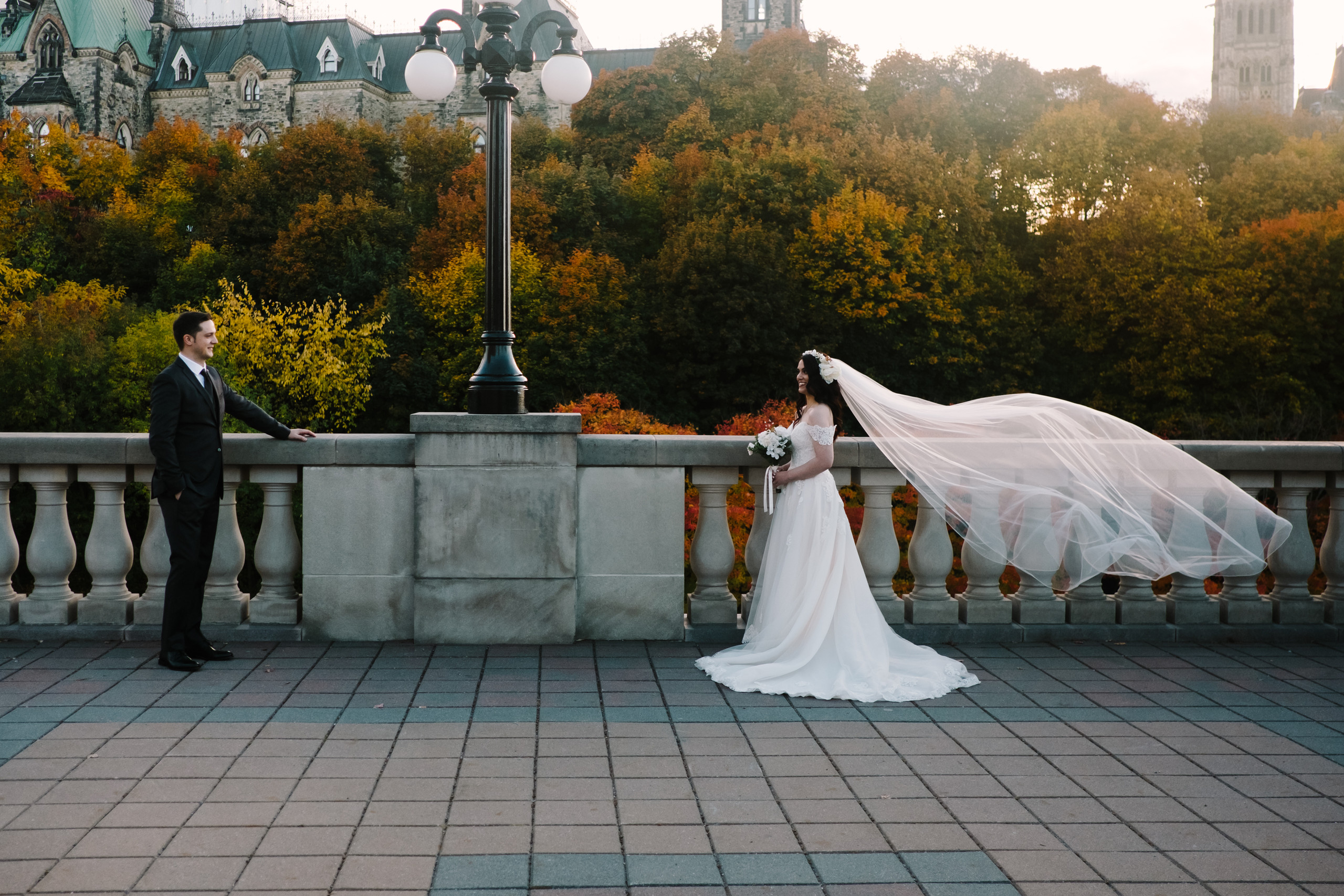 Bride and groom at the Château Laurier with bride's veil blowing in the wind. Photo was taken in the Fall with the changing leaves in the background. Photo by Melanie Mathieu Photography.