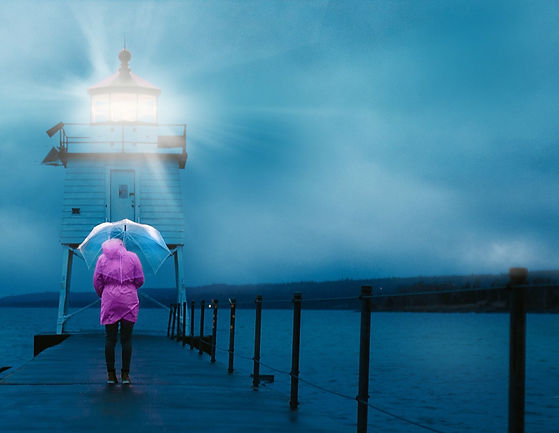 A woman in a pink raincoat with an umbrella. She is standing next to a lighthouse