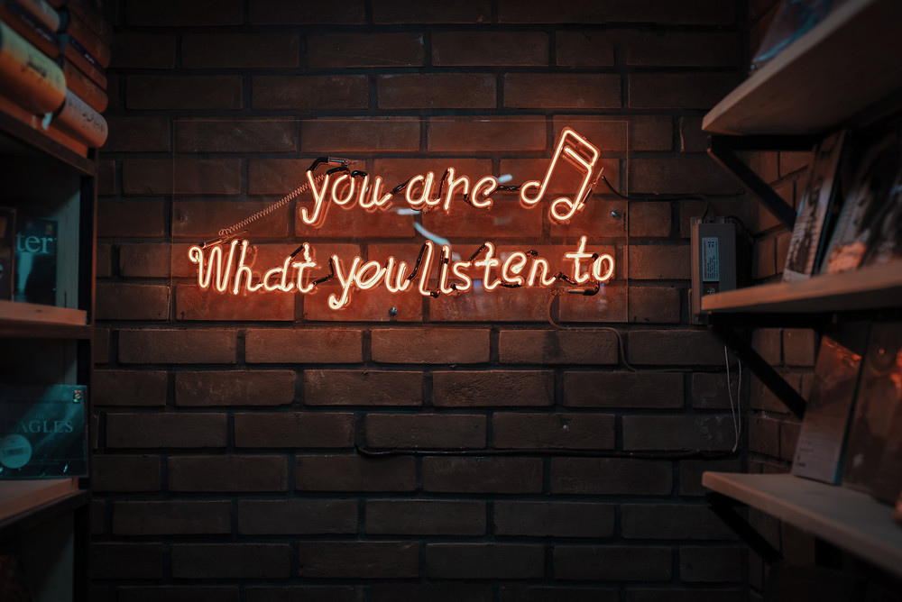 photo of a neon sign saying you are what you listen to
