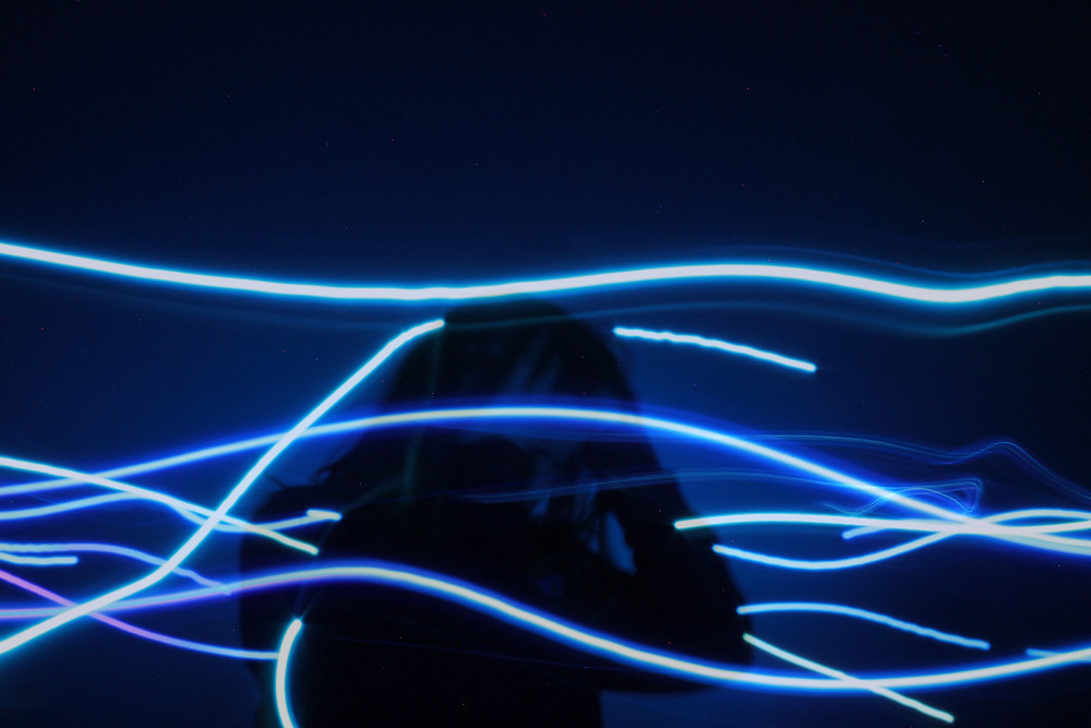 photo of a woman's silhouette with neon blue lines around it