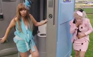 Kath & Kim at the Melbourne Cup. They are both visibly drunk. Kim is stumbling out of a porta-loo and kath is holding her hand over her mouth to catch her vomit.