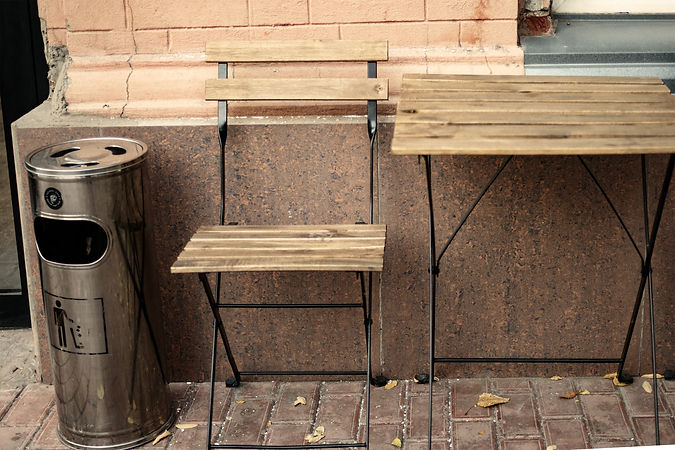 Wooden table and chair outside cafe with