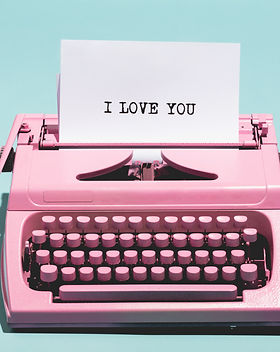 Pink vintage typewriter with a white sheet of paper and _I love you_ written on it. Love c