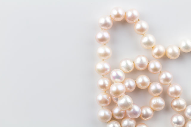 Pearl necklace background with a string of pink pearls isolated on white background - top