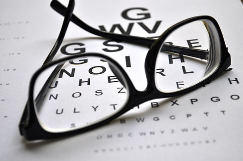 Eyeglasses on eye charts background clos