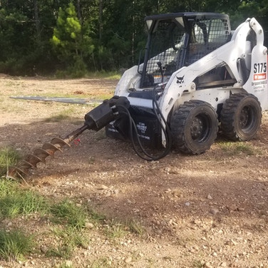 Our bobcat ready to drill some fence post holes