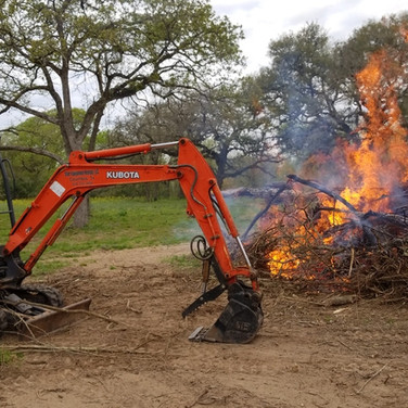 Burning a brush pile and stoking it with our mini-ex.