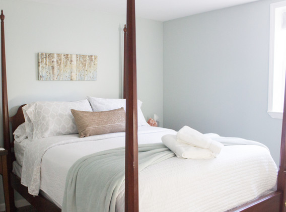Vintage 4-poster bed and Sealy queen matress in this bright and cheery room that boasts a full sized window.