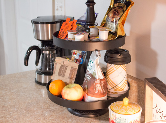 The coffee station is stocked with creamer, sugar, honey, tea, and snacks.