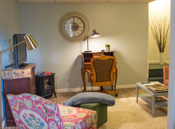 TV with cable, a small work desk, Amazon Echo, a space heater, love seat, chair, and eating bar (the vintage ironing board) are some of the features of the living room! There are no windows in this room, but the light from the bedroom streams in, especially in the afternoon!