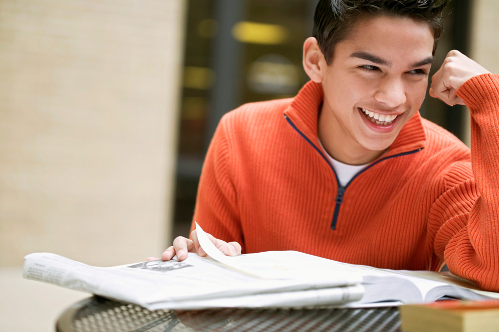 smiling student (boy) sitting at desk with textbook