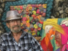 Smiling man in front of artwork