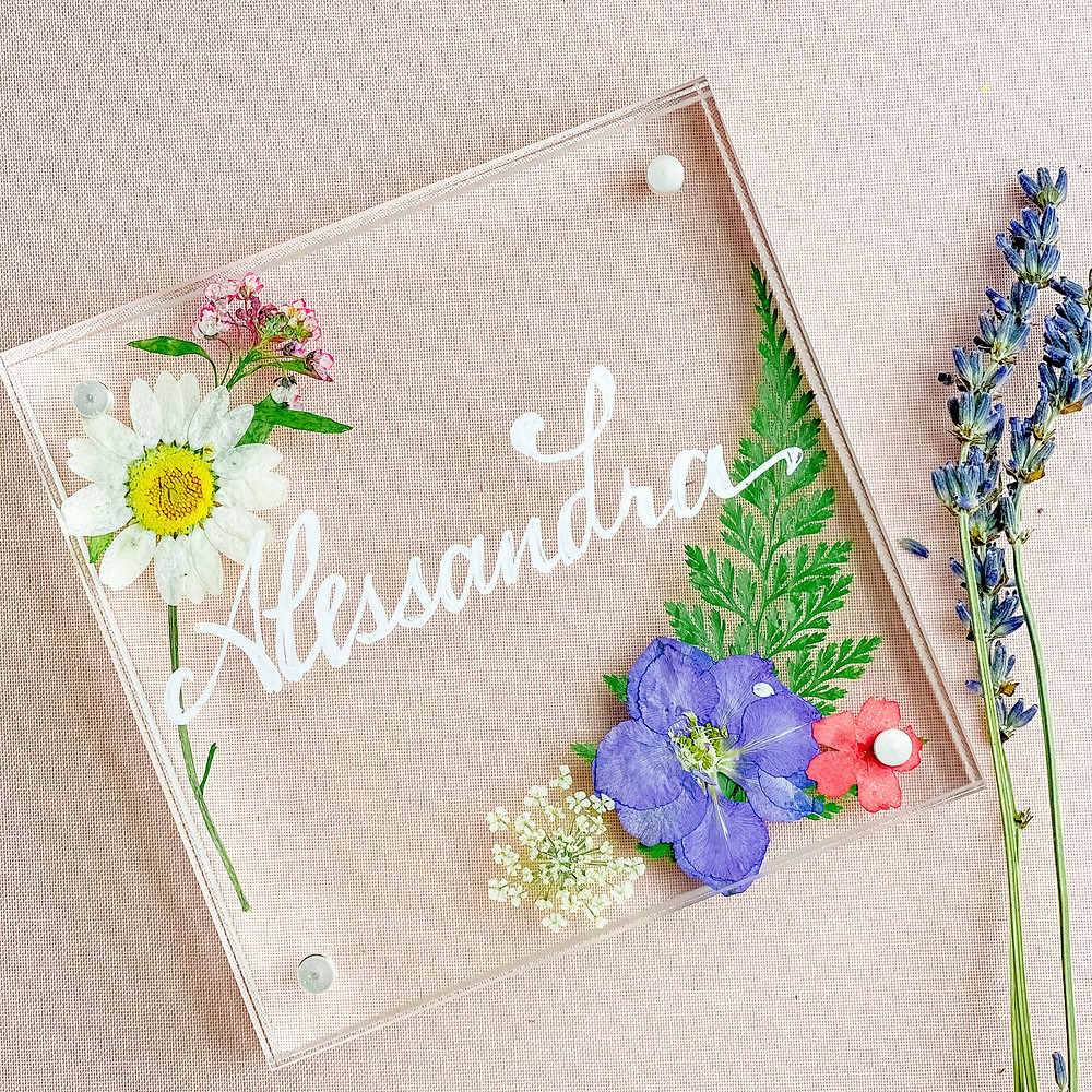 pressed flowers in an acrylic frame with a personalized name