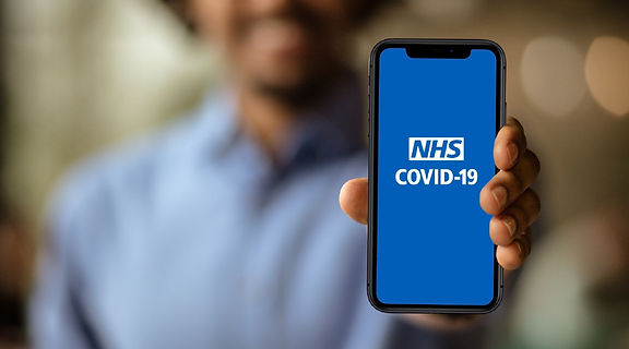 Person holding smartphone showing NHS COVID app.jpeg