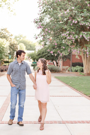 engagement photos cute couple walking holding hands flowering trees Milledgeville GA Georgia College and State University
