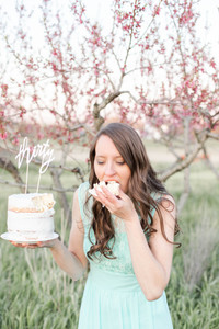 pretty woman in field at sunset eating cake