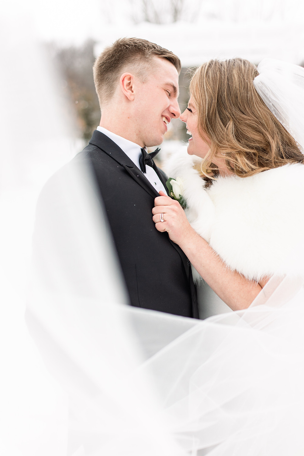 Josh and Andrea wedding photography husband and wife photographer team michigan venue Bay Pointe Woods shelbyville snow winter wedding bride and groom kissing laughing