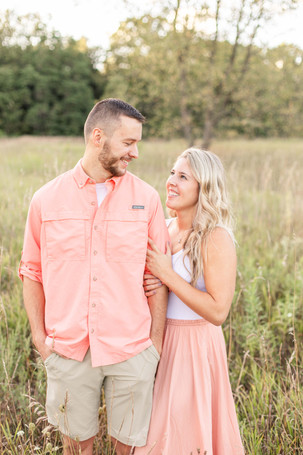 Engagement Photos Al Sabo Land Preserve Kalamazoo Michigan cute couple smiling holding arms in Open Field
