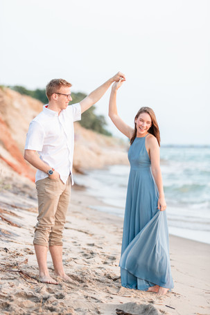 Engagement Photos Tunnel Park Beach Holland Michigan Engaged Couple twirling on beach long blue dress