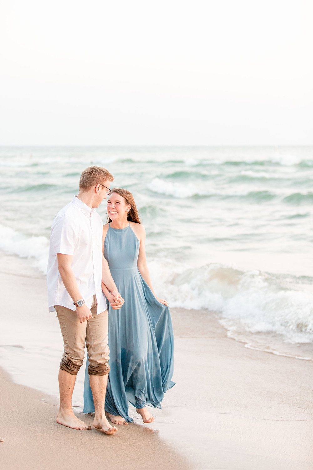 Engagement Photos Tunnel Park Beach Holland Michigan Engaged Couple walking on beach smiling long blue dress