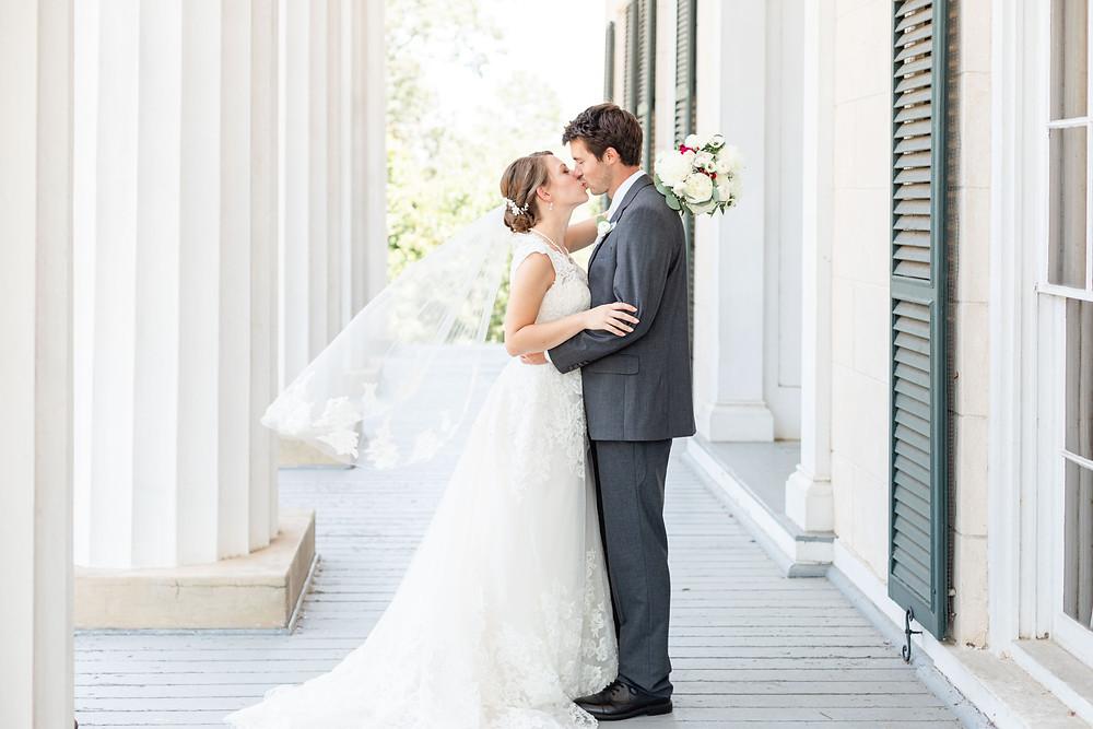 Bride and Groom kissing Rose Hill Antebellum Lockerly Arboretum Milledgeville Georgia Wedding Veil Flying