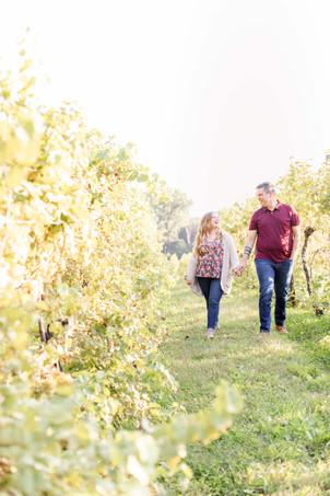 Engagement photos Round Barn Winery Baroda Michigan vineyard cute couple walking holding hands laughing