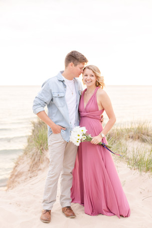 south haven man and women smiling beach engagement photos standing